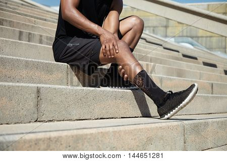 Sports Injury Concept. Cropped Portrait Of Black Male Runner Wearing Black Training Outfit Touching