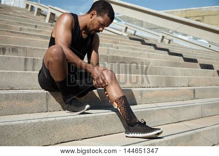 Black Male Jogger In Black Sportswear And Athletic Shoes Sitting On Stair Outdoors Clutching His Ach