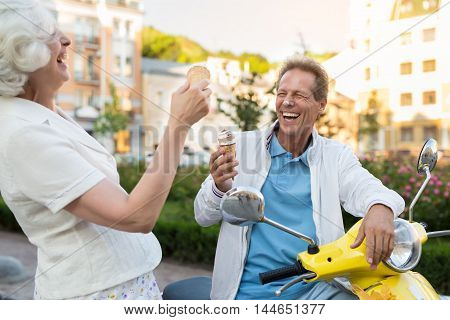 Couple with ice cream laughing. Nose smeared in ice cream. Joke around all day. Funniest moments on vacation.