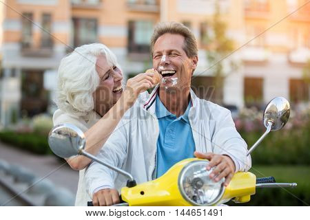 Guy's face in ice cream. Mature couple is laughing. Magic of summer. Look at yourself, sweetie.
