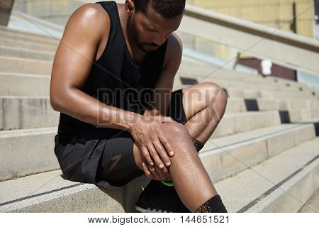 Handsome Muscular Male Jogger Wearing Black Training Outfit Touching His Knee In Pain With Clasped H