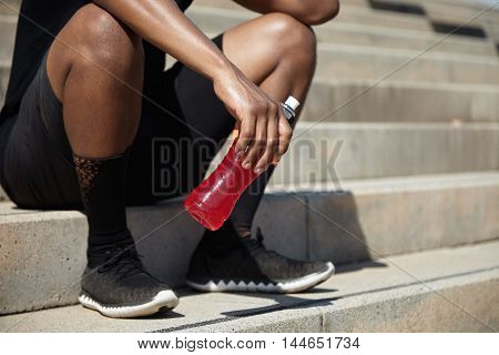Young African Jogger With Muscular Legs Relaxing After Evening Run On Embankment, Sitting On Sidewal