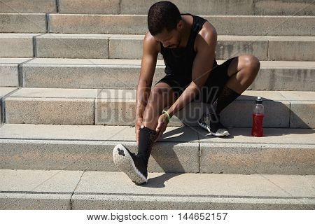 Dark-skinned Athlete With Muscular Body Wearing Black Outfit Holding His Injured Leg With Both Hands