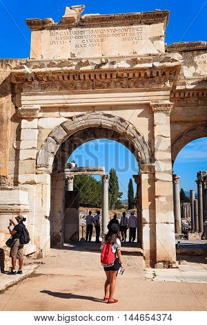 EPHESUS, TURKEY - SEPTEMBER 30, 2014: Tourist with a guide at the Gate in Ephesus