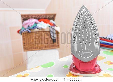 Beautiful a modern iron on an ironing board.