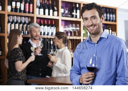 Smiling Man Holding Wineglass While Friends Standing In Backgrou