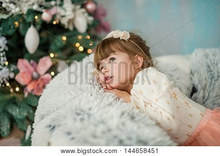 The little girl looks dreamily on the tree in anticipation of holiday