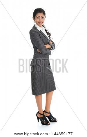 Full length portrait of businesswoman standing arms crossed isolated on white background. Mixed race Asian Indian and African American model.