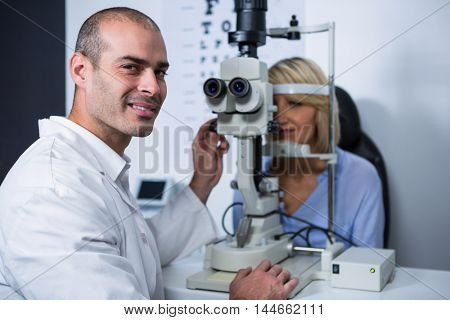 Portrait of smiling optometrist examining female patient on slit lamp in ophthalmology clinic