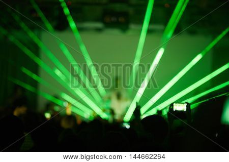 Defocused image of crowd enjoying performance and musician on stage in bright green rays of strobe lights