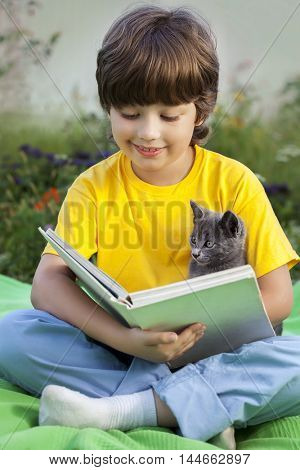 Boy reading book with kitten in the yard, child with pet reading magazine on the grass in the park