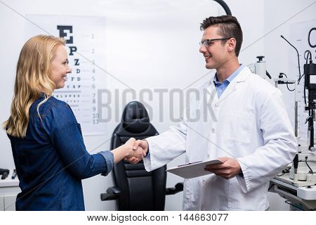 Optometrist shaking hands with female patient Optometrist shaking hands with female patient