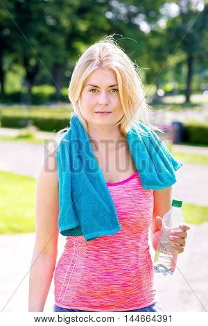 Young blond woman in pink top with blue towel around neck and half empty water bottle in hand while recovering from a long run