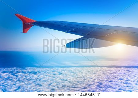 Wing of airplane flying above cumulus clouds. View of sky from aircraft long distance travel by airtransport. Russia
