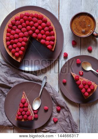 Homemade chocolate cheesecake cake with fresh raspberries and hot coffee on the rustic wooden table. Concept of a romantic breakfast. Horizontal top view.