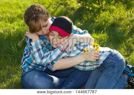 Mother and son in the park on the grass hugging