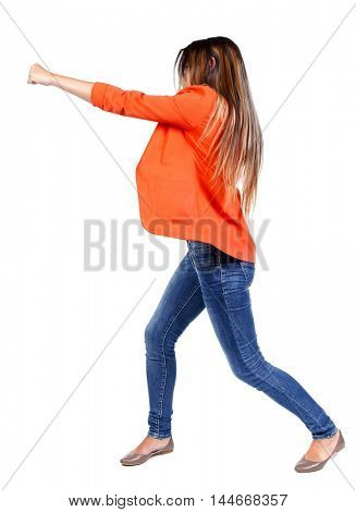 back view of woman funny fights waving his arms and legs. business woman in a red jacket hand strikes.
