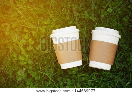 Two white paper cups of coffee to go on the grass. Place for your text or logo on cups.