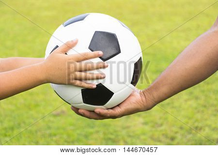 child with soccer ball  and coach on background green grass.