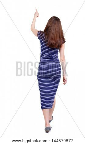back view of pointing walking woman. going girl pointing. backside view of person. brunette in a blue striped dress went off showing thumb up.