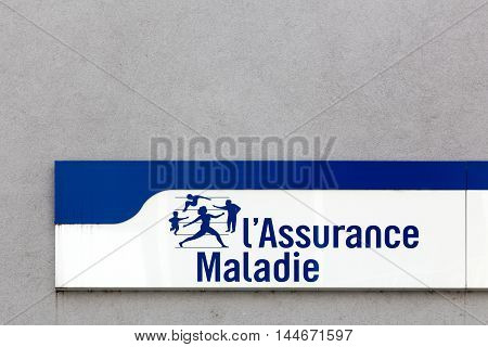 Firminy, France - August 17, 2016: Social security sign on a wall. Illness branch called Assurance Maladie is one of the four branches with retirement, family, work accident and occupational disease in France