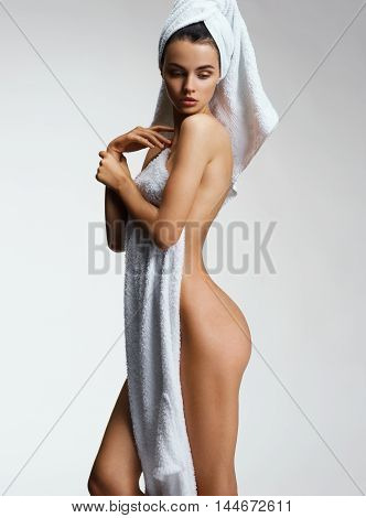 Well-groomed slim girl after bath with towel. Photo of Woman show her tan slim body. . Wellness and Spa concept