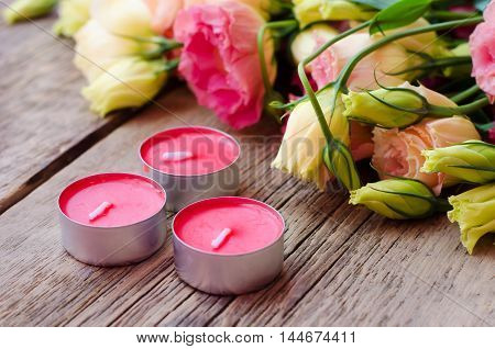 Scented candles on wooden background next to a bouquet of roses French