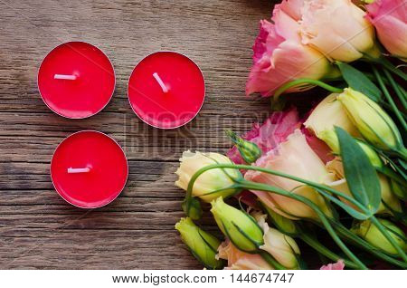 Scented candles on wooden background with a bouquet of flowers near the top view