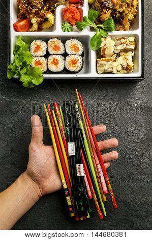 Мужская рука держит палочки, которые используют для того, что бы кушать суши