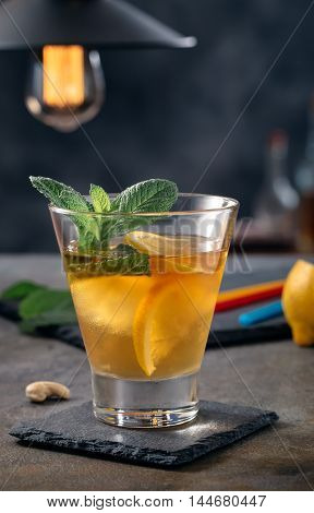 Glass of bourbon based cocktail with lemon and mint