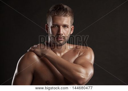 Model man with an open chested on a dark background muscular body of a young man in jeans . Shot in a studio .
