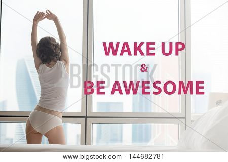 Back view of young woman stretching after waking up doing morning exercises at home. Female model relaxing and looking at misty city scenery in the window. Motivational phrase
