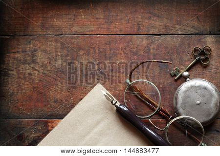 Old spectacles near closed pocket watch and pen on wooden background