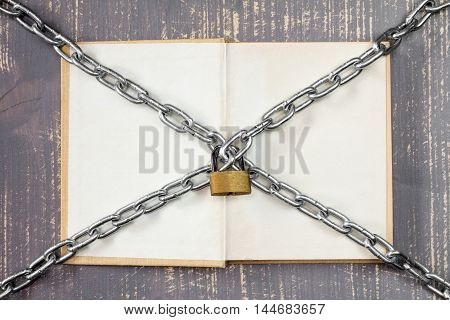 Open book with chain and padlock on wooden background.