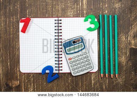 Digital calculatoropen notebookcolor numbers and pencil.Top view.