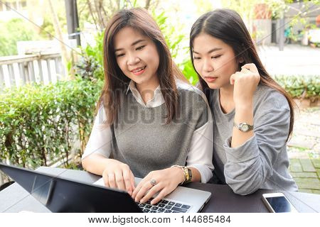 Happy Two Asian Woman Using Laptop Computer And Business Talking