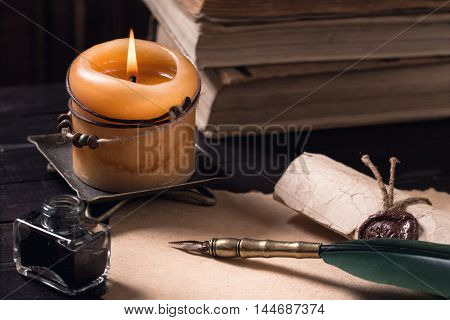 Letter, quill pen with lighted candle and pile of old books on dark background still-life