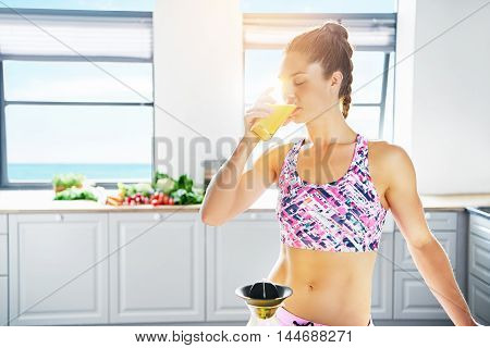 Fit young woman drinking a glass of fresh orange juice that she has just prepared on a juicer against a high key kitchen background in a healthy lifestyle and diet concept