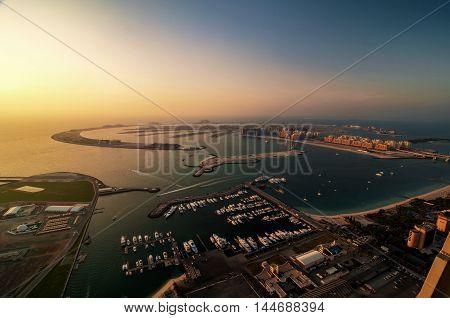 Majestic colorful dubai palm island during beautiful sunset. Amazing dock with several luxury yachts and extraordinary island. Dubai marina United Arab Emirates.