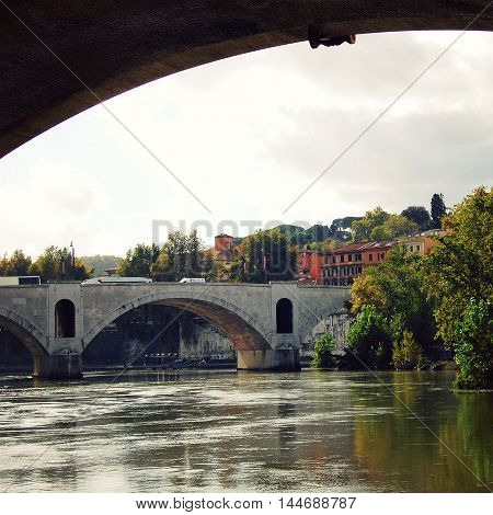 Tiber river and a PASA bridge in Rome. Ponte Principe Amedeo Savoia Aosta (also known as Ponte PASA). View from an arch of Ponte Vittorio Emanuele II.
