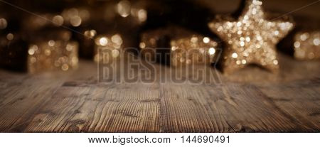 Wooden table with christmas stars in background