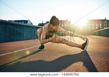 Sun highlights young muscular female athlete as she stretches preparing to run