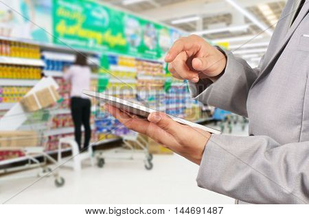 Hand Of Businessman Use Mobile Tablet In Supermarket