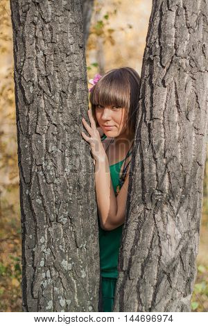 Portrait of a beautiful girl in green dress stands between two trees in autumn park