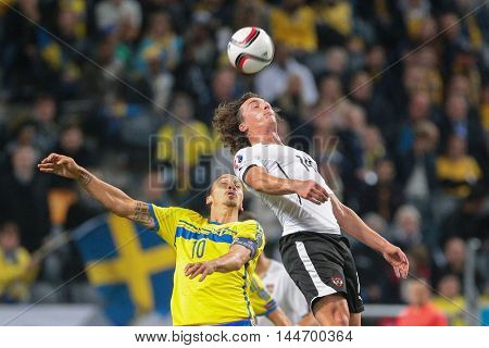 STOCKHOLM, SWEDEN - SEPTEMBER 8, 2015: Zlatan Ibrahimovic (Sweden) and Julian Baumgartlinger (Austria) fight for the ball in an European Championship qualification game.