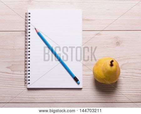 Blank notebook with pencil and pear on wooden table. Diet and nutrition concept