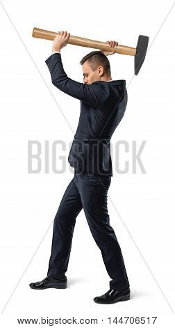 Businessman standing side view to the camera in a suit raising a big mallet above his head in a conceptual image isolated on white