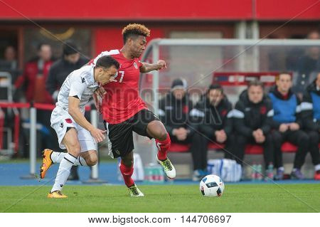 VIENNA, AUSTRIA - MARCH 26, 2016: Ergys Kace (Albania) and David Alaba (Austria) fight for the ball in a friendly football game.