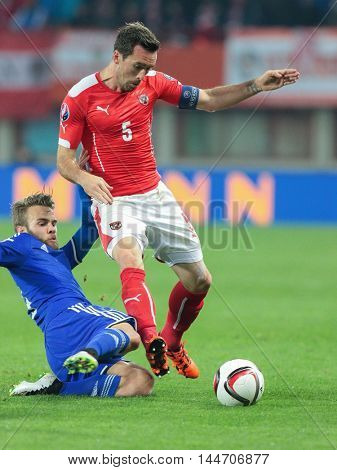 VIENNA, AUSTRIA - OCTOBER 12, 2015: Niklas Kieber (Liechtenstein) and Christian Fuchs (Austria) fight for the ball in an European Championship qualification game.