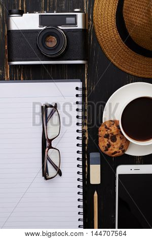 Close-up of working table mockup with hat, notepad, old-fashioned camera, phone, eyeglasses and a cup of coffee with cookie on it